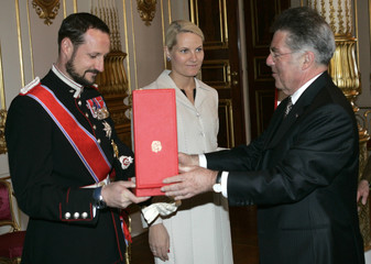 Austria's President Heinz Fischer hands over Austrian Medal of Honour to Norwegian Crown Prince Haakon and his wife Princess Mette Marit at Royal Palace in Oslo