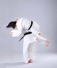 Young sporty women practicing martial arts on light background