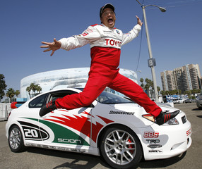 Actor Carlos Mencia jumps during a news practice day for the 2009 Toyota Pro/Celebrity car race in Long Beach