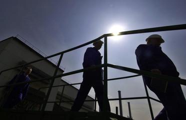 Macedonian workers walk on a bridge in a steel factory in Makstil.