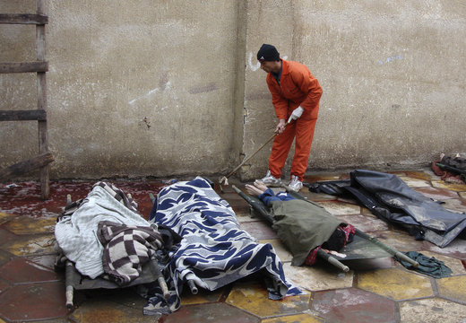 A worker cleans the floor beside the bodies lying in Yarmouk hospital morgue compound in Baghdad