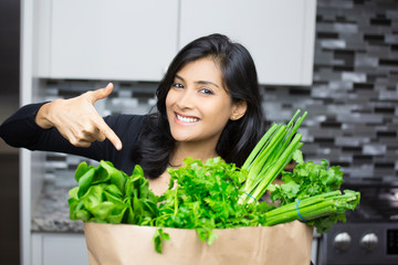 Closeup portrait, young woman pointing to bag full of green groceries, healthy nutritious balanced diet, isolated indoors home background. Locally sourced food