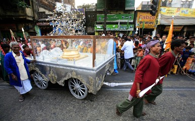 Men pull a hand cart with silver tree during a Jain religious procession in Kolkata