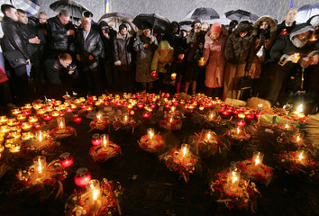 People place candles in a monument commemorating the mass famine of 1932-33 in Kiev