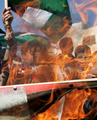 Palestinian school boys burn a Danish flag during a protest against cartoons depicting Prophet Mohammad in Hebron