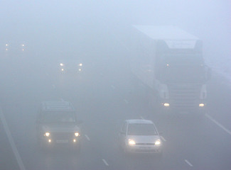 Cars drive in thick fog on the M1 motorway in central England