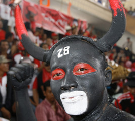 A supporter of the Indonesia Democratic Party - Struggle, who is dressed and coloured as the party's symbol of a buffalo, smiles during rally in Surabaya