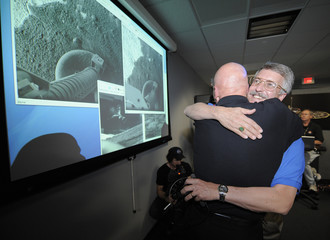 Ed Sedivy hugs Doug McCuiston as images downloaded from the Phoenix Mars Lander are projected on screens in the control room at the JPL in Pasadena