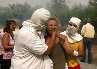 Two men evacuate a crying woman from her home during a forest fire in Anthousa suburb north of Athens