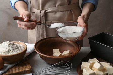 Woman making dough for a pie in bowl