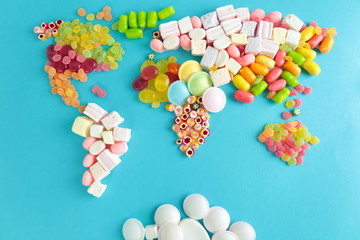 Fototapete - Map of world made from different candies on blue background