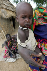 File photo of a starving Sudanese child holding onto her mother as they wait in line at a feeding ...