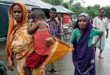 A Bangladeshi flood victim takes her blind mother to a relief centre to collect relief goods in Dhun..