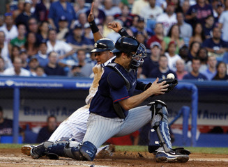 Yankees' Cabrera slides into home to score as Twins catcher Mauer bobbles ball in MLB baseball action from New York