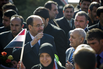 Iraq's Prime Minister Nuri al-Maliki waves to his supporters after arriving at International Mehrabad airport in Tehran