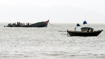Residents try to fish out a sunken boat in Vietnam's central resort city of Danang