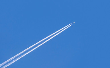 Diagonal trace of plane flying in blue sky