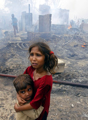 AN INDIAN SLUM GIRL WEEPS WHILE HUGGING HER BROTHER AFTER A FIRE IN NEW DELHI.