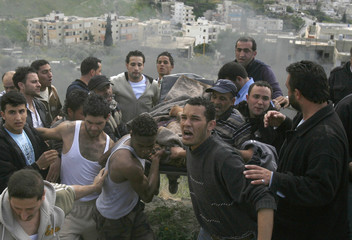 Palestinian men carry a body from a burnt car at the site of an explosion in Mieh Mieh refugee camp outside Sidon