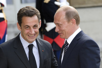 France's President Nicolas Sarkozy speaks with Russia's Prime Minister Vladimir Putin as he arrives for dinner at Elysee Palace