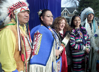 CANADIAN BOBSLEDER SMITH POSES WITH NATIVE AMERICAN DANCERS.