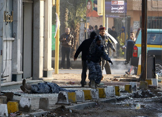 Iraqi policemen react as a wounded colleague lies on the ground shortly after a bomb attack in central Baghdad
