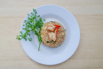 Stir fried rice in white plate on wooden table, close up fried rice, Thai food