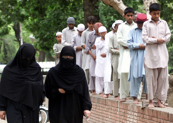 PAKISTANI WOMEN WALK PAST A MOSQUE DURING FRIDAY PRAYERS IN ISLAMABAD.