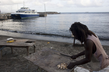 A local cuts seafood on a beach in Basseterre