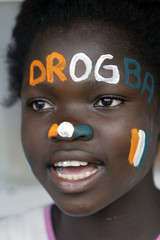 A girl with her face painted with Ivory Coast's flag colours and the name of Ivory Coast soccer play..