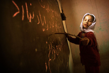 AFGHAN GIRL READS FROM BOARD AT HOME-BASED SCHOOL IN KABUL.