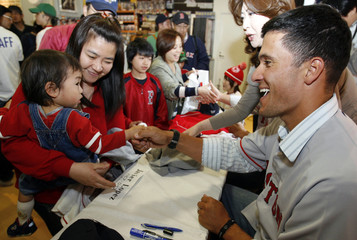 Japanese child shakes hands with Boston Red Sox pitcher Lopez during event at MLB merchandise shop in Tokyo