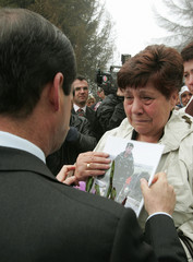 SPANISH DEFENCE MINISTER JOSE BONO MARTINEZ CONSOLES A SPANISH WOMAN CARRYING PICTURE OF HER SOLDIER SON.