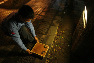 An exterminator picks up a trap with dead rats outside a shopping centre in Taiwan