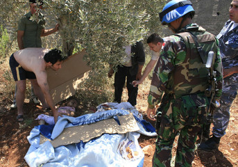 An Indonesian U.N. peacekeeper and civilians inspect the bodies of a family after a crash in Mays al-Jabal village, southern Lebanon