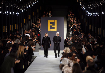 Designers Lagerfeld and Venturini Fendi for fashion label Fendi walk down the catwalk after their fashion show on the Great Wall of China near Beijing