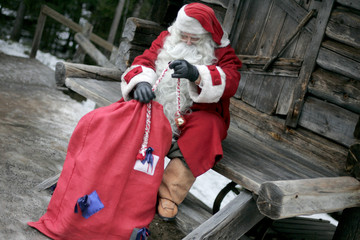 A man dressed as Santa Claus rides prepares a bag of toys for Christmas on the Arctic Circle in Rovaniemi, northern Finland