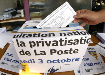 """A person casts a ballot for a national popular vote about the privatization of """"La Poste"""" in Nice"""