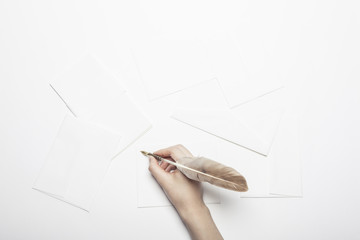 woman hand hold a fountain pen with letter on the white table.