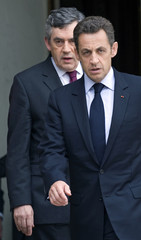 France's President Sarkozy annd British Prime Minister Brown walk to a press conference in Paris