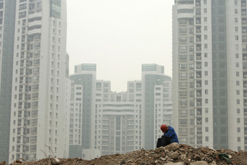 A migrant worker rests at a construction site in Shanghai