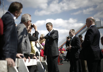 US President Obama checks his watch as he greets wellwishers upon his arrival in Fort Myers