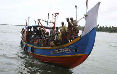 Fishermen arrive at a fishing harbour after they were rescued when their boat sank in the sea in Kochi