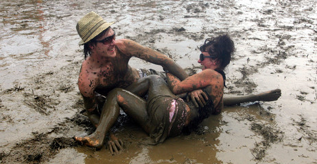 Revellers wrestle in the mud on the first day of the Glastonbury music festival in Somerset southern England.