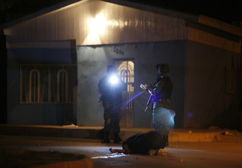 A soldier takes notes as another one takes pictures of the body of a woman gunned down in an impoverished neighbourhood of the border city of Ciudad Juarez