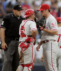 Phillies catcher Ruiz talks with relief pitcher Lidge as homeplate umpire Knight listens, against the Atlanta Braves in Atlanta