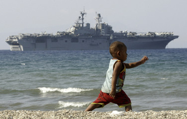 An East Timorese child runs on Dili beach