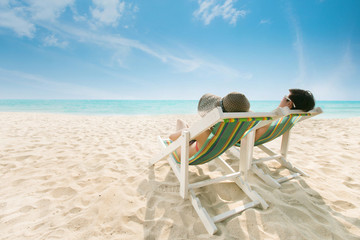 Couple sunbathing on a beach chair The beach is bright blue. During the summer