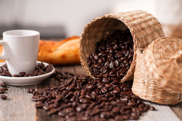 Cup of coffee and coffee beans on wood table