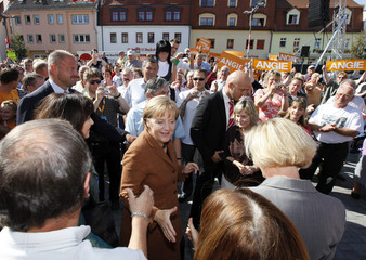 German Chancellor Merkel shakes hand with people as she arrives to an election campaign rally in Finsterwalde